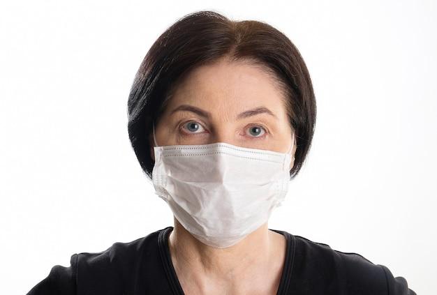 Starzejąca się kobieta w medycznej masce ochronnej na bielu