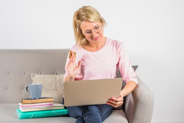 Starzejąca się kobieta w różanej bluzce z klingerytów kartą, laptopem i filiżanką na rozsypisku książki na kanapie