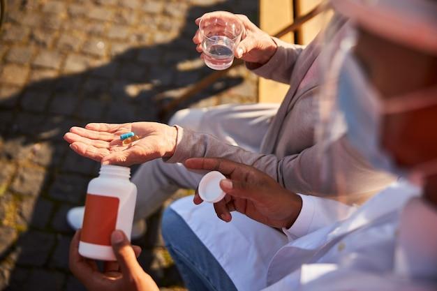 Starzejąca się osoba siedząca na ławce z niebieskimi i pomarańczowymi pigułkami w dłoni, trzymająca szklankę wody