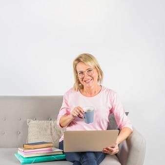 Starzejąca się uśmiechnięta kobieta w różanej bluzce z laptopem i filiżanką blisko rozsypiska książki na kanapie