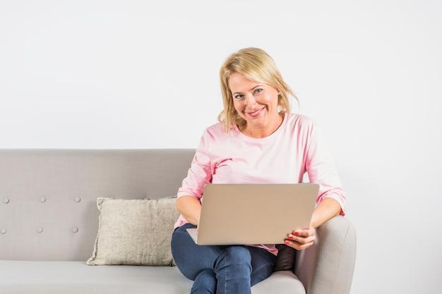 Starzejąca się uśmiechnięta kobieta w różanej bluzce z laptopem na kanapie