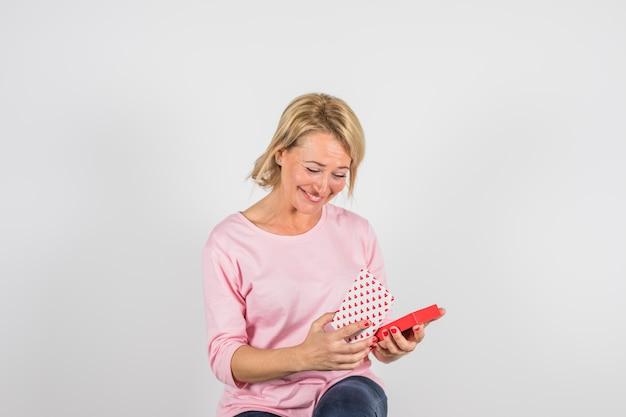 Starzejąca się uśmiechnięta kobieta w różanej bluzce z teraźniejszości pudełkiem