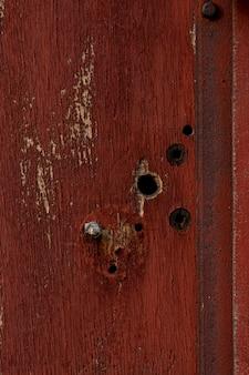 Starzejące się drewno z dziurami i zardzewiałym metalem