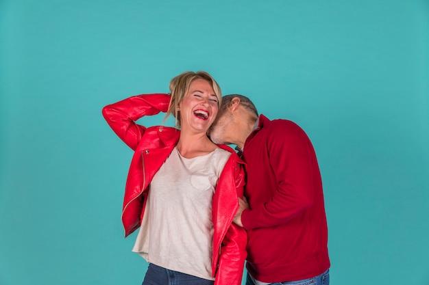 Starzejący się mężczyzna całuje uśmiechniętej kobiety