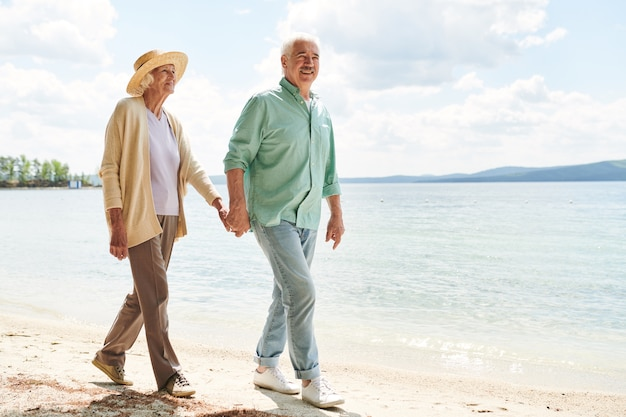 Starzejący się mężczyzna i kobieta, trzymając się za ręce, relaksując się na plaży wzdłuż wybrzeża w upalny letni dzień