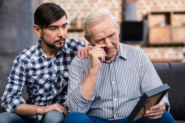 Starzejący się mężczyzna trzymający ramkę na zdjęcia i wspominający swoją przeszłość z synem
