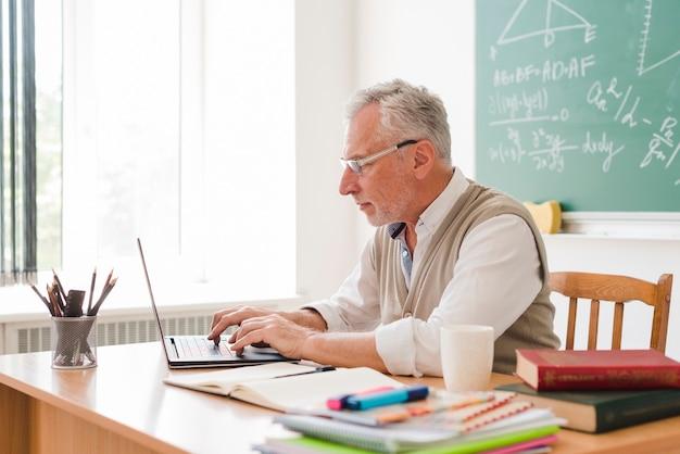 Starzejący się nauczyciel pracuje przy laptopem w sala lekcyjnej