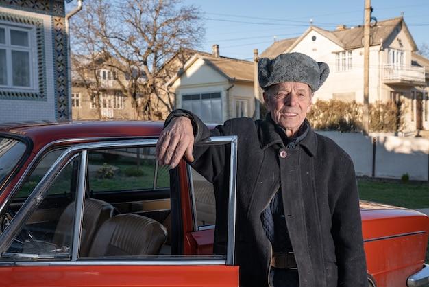 Starzejący się ufny mężczyzna w szarej retro kapeluszowej pozyci na jego jardzie blisko jego czerwonego starego samochodu