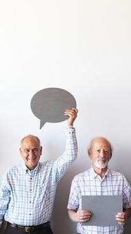 Starzy ludzie pokazujący puste przemówienia bąbelkowe