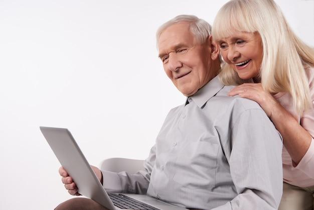 Starzy ludzie współdziałają z nowoczesną technologią.