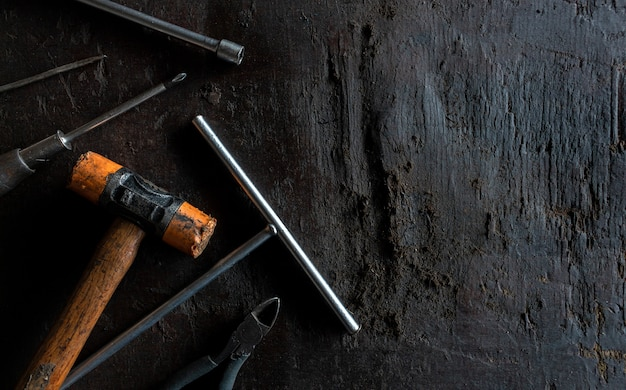 Starzy narzędzia na czarnym drewnianym podłogowym tle