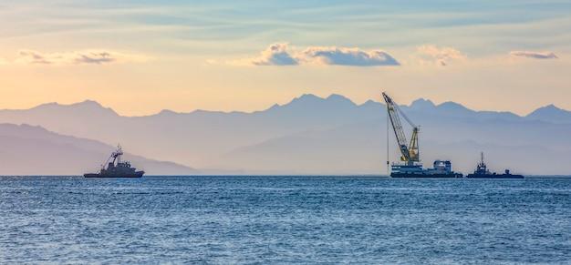 Statek morski z dźwigiem na tle pasma górskiego we mgle
