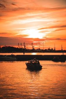 Statek na morzu z pięknym zachodem słońca odbijającym się na powierzchni
