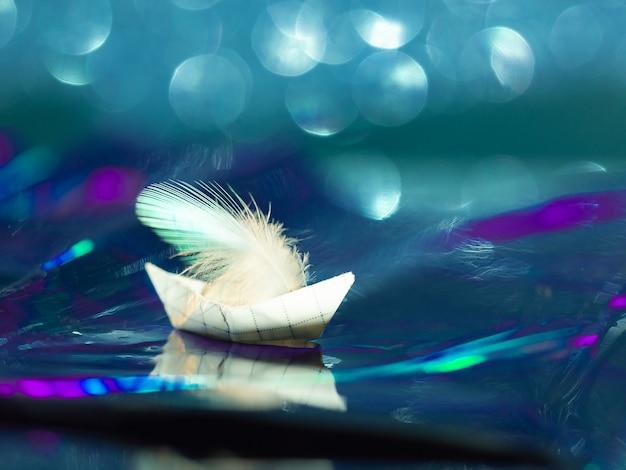 Statek origami pływający po falach morza, wykonany z kolorowego błyszczącego papieru z bokeh.