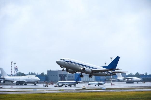 Statek pasażerski startuje w niebo z pasa startowego lotniska w pochmurną pogodę z deszczem