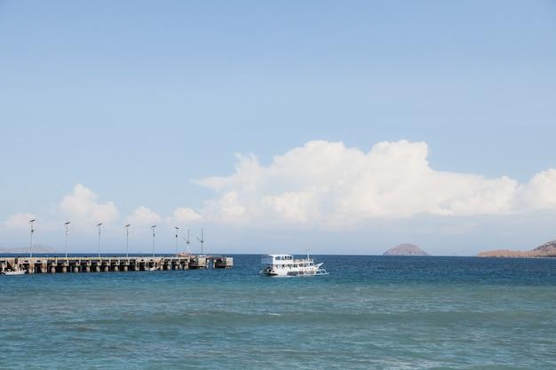 Statek phinisi płynący po morzu mijając molo