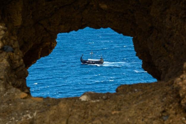 Statek piracki na otwartym morzu o zachodzie słońca. statek wikingów na morzu