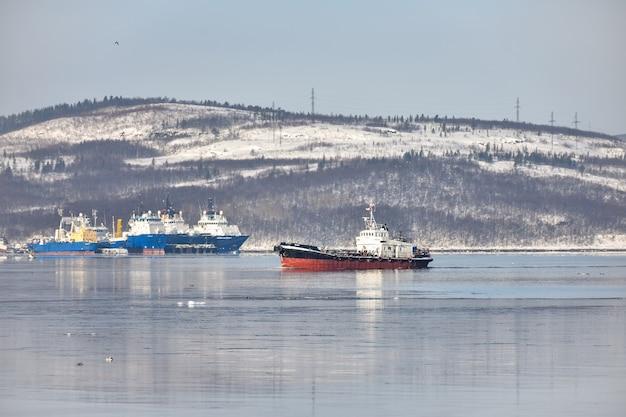 Statek płynący po morzu na tle ośnieżonych gór