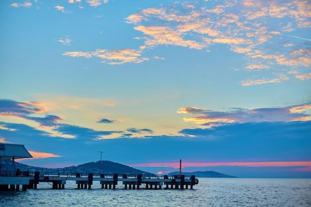 Statek płynie o zachodzie słońca nad cieśniną bosfor w stambule.