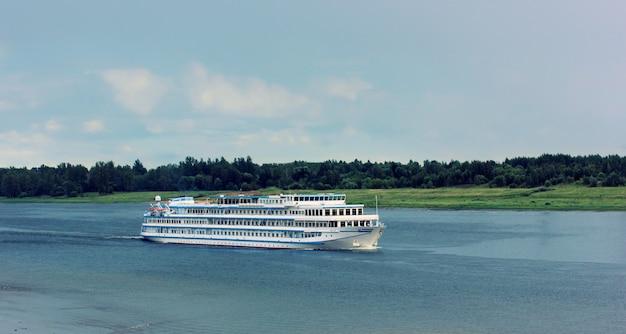 Statek płynie wzdłuż rzeki wzdłuż brzegu z drzewami