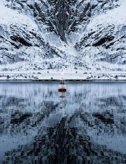 Statek pływający po potężnej górze w dolinie w zimie