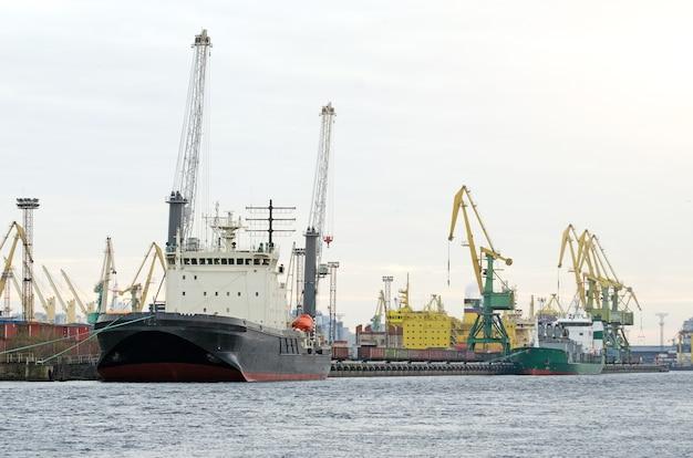 Statek towarowy i kontener towarowy współpracujący z dźwigiem na terenie portu, logistic import export.
