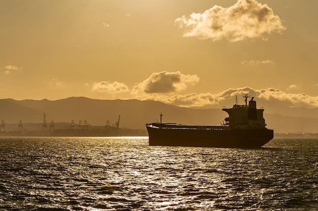 Statek towarowy na drodze o zachodzie słońca. import i eksport logistyki.
