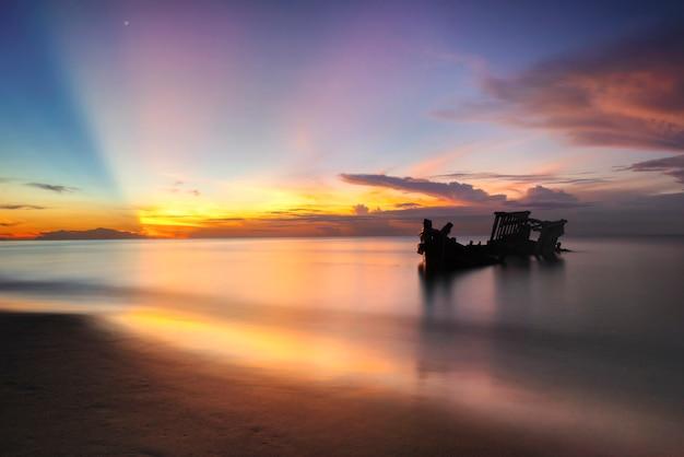 Statek wrak łodzi rybackiej na plaży o wschodzie słońca