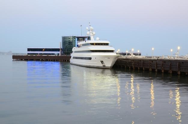 Statek wycieczkowy cumuje wieczorem przy molo na bulwarze bakuu