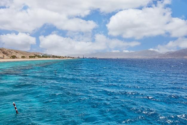 Statek wycieczkowy do podróży po morzu czerwonym w izraelu. na tle wybrzeża i gór.