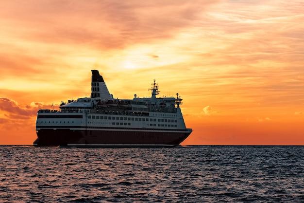 Statek wycieczkowy na otwartym morzu. żeglowanie promem pasażerskim na gorący zachód słońca