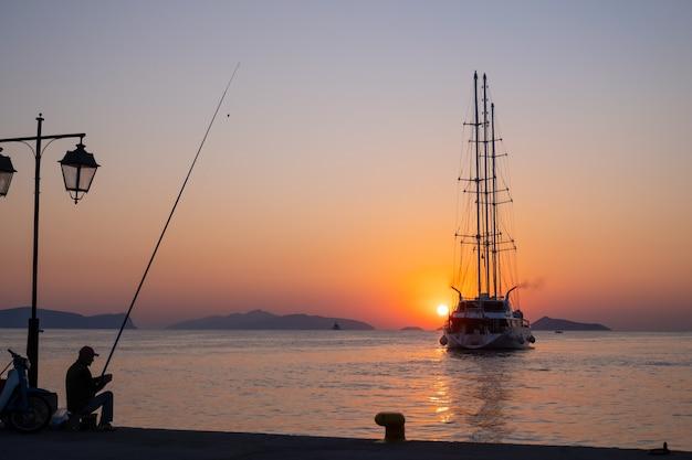 Statek wycieczkowy płynie na tle pomarańczowego zachodu słońca