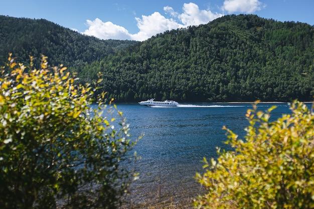 Statek wycieczkowy płynie po niebieskiej, czystej wodzie na tle zielonych zalesionych wzgórz