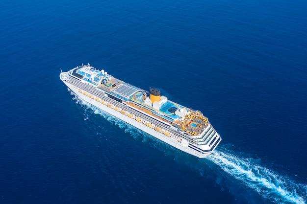 Statek wycieczkowy pływa w niebieskim morzu pozostawiając pióropusz na powierzchni morskiego krajobrazu. widok z lotu ptaka koncepcja podróży morskich, rejsy.