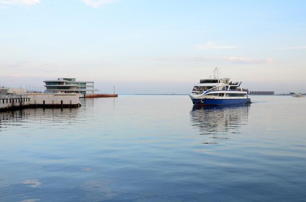 Statek wycieczkowy przypływa wieczorem do przystani na bulwarze baku