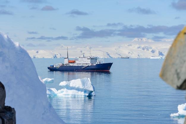 Statek wyprawowy z górą lodową na morzu antarktycznym