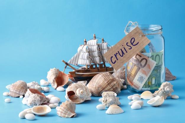 Statek zabawkowy, słoik pieniędzy i muszle