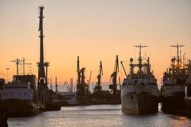Statki w porcie morskim na tle zachodu słońca. krajobraz przemysłowy z dźwigami kontenerowymi i statkami.