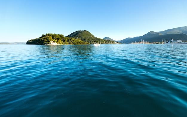 Statki wycieczkowe w zatoce. mgliste lato krajobraz wybrzeża lefkady (nydri, grecja, morze jońskie).