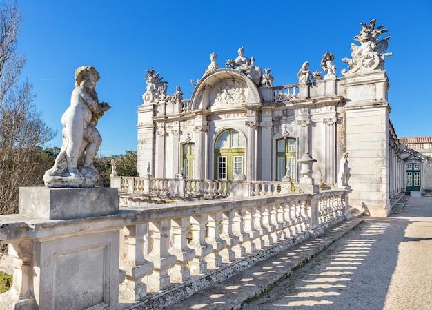 Statua amora na tle fasady starego zamku królewskiego. queluz, sintra.