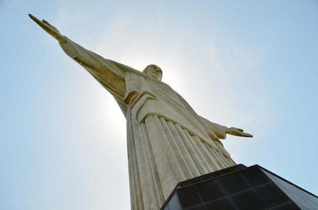 Statua chrystusa odkupiciela - rio de janeiro-brazylia - z zachodem słońca za nim.