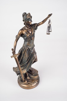 Statua lady justice to starożytna grecka bogini, która jest symbolem sprawiedliwości na białym tle.