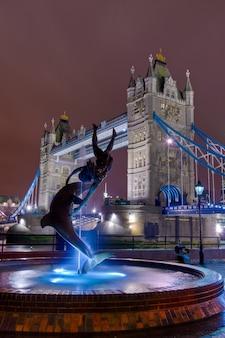 Statua skierowana w stronę wieży most nocą