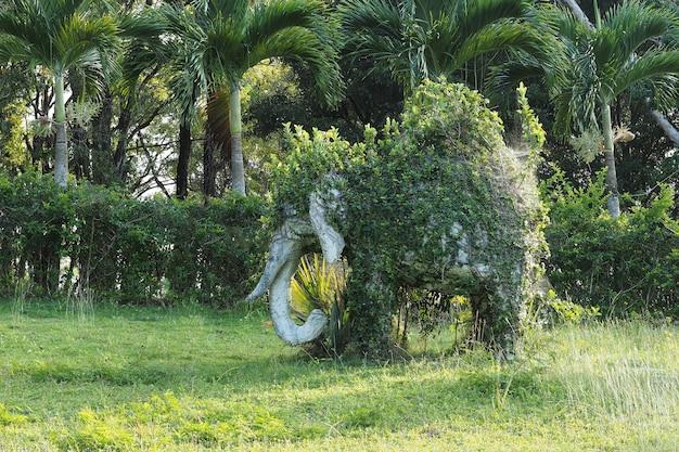 Statua słonia w parku porośniętego krzakami