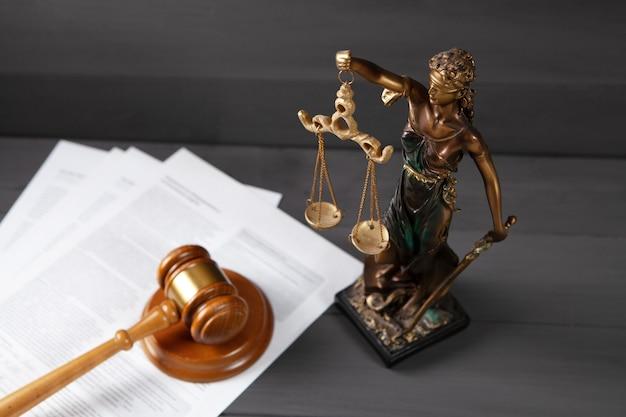 Statua sprawiedliwości i młotek na szarej powierzchni