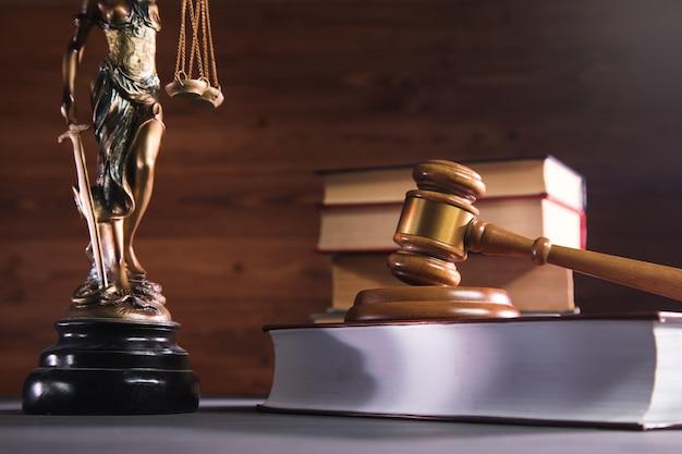 Statua sprawiedliwości, książka i młotek na drewnianym stole