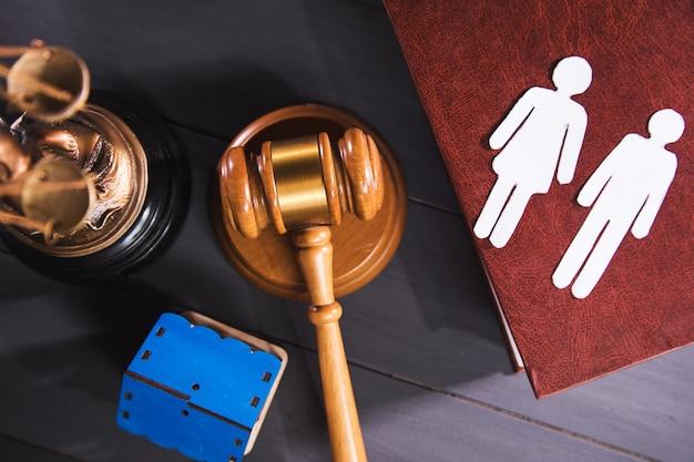 Statua sprawiedliwości, młot i ludzie na stole. biznes rodzinny