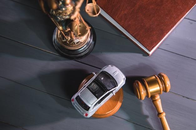 Statua sprawiedliwości, młotek i samochód na drewnie. próba