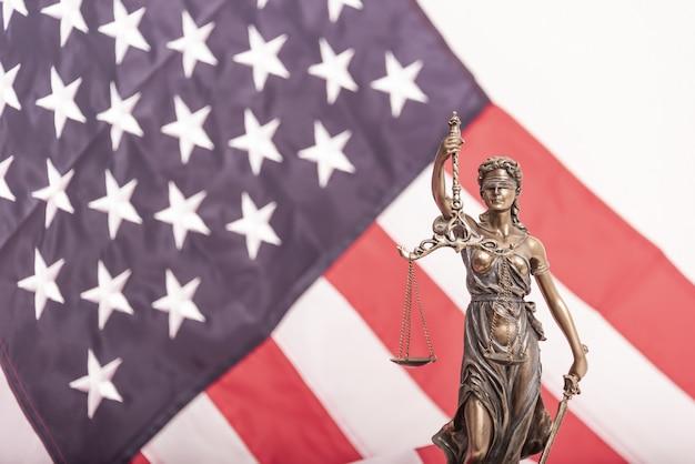 Statua sprawiedliwości themis lub iustitia, bogini sprawiedliwości z zawiązanymi oczami na tle flagi nie...