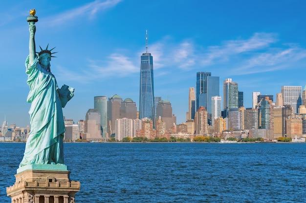 Statua wolności na tle panoramy miasta manhattan, zabytki nowego jorku, usa